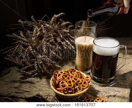 Foamy beer from bottle poured into glasse standing with mug beer with wheat and basket of pretzels on linen cloth on wooden background