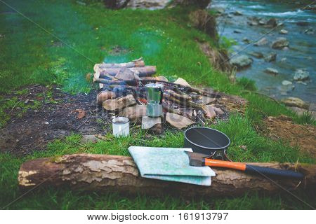 log is lying near a campfire which is near the river a map and an ax lying on a log pot mug and coffee geyser on the grass near a campfire.
