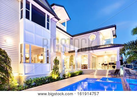 Beautiful and attractive house at coast in the night with the blue lights in swimmimg pool