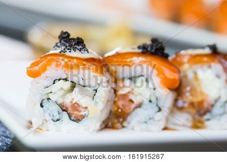 Sushi salmon roll on white dish in the restaurant