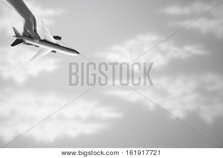 Closeup of woman's hand flying toy plane upside down against cloudy sky