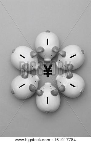 Piggy banks surrounding a Yen Yuan symbol view from above