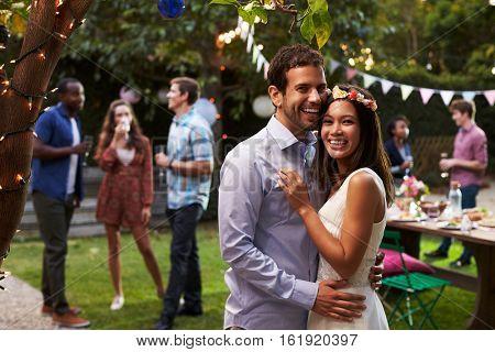 Portrait Of Couple Celebrating Wedding With Backyard Party