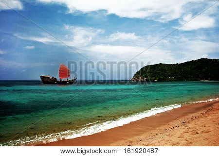 Sailboat with red sails in a tropical bay