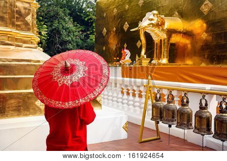 Woman tourist with red traditional Thai umbrella in Golden temple Wat Phra Singh in Chiang Mai Thailand