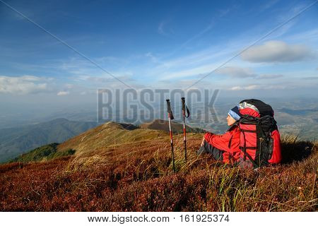 Tourist halt in mountains. Woman has bright red outdoorsy clothing. Sky and mountain ranges in background. Red bilberry leaves in foreground.