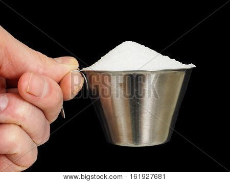 Person holding a measuring cup of one deciliter filled up with white granulated sugar isolated on black