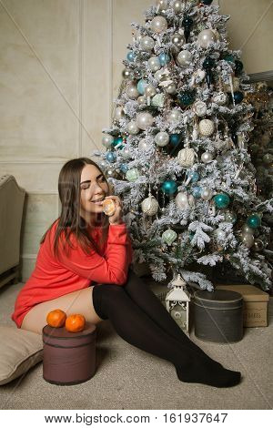 attractive woman in a sweater and stockings sitting under the Christmas tree and eat a tangerine