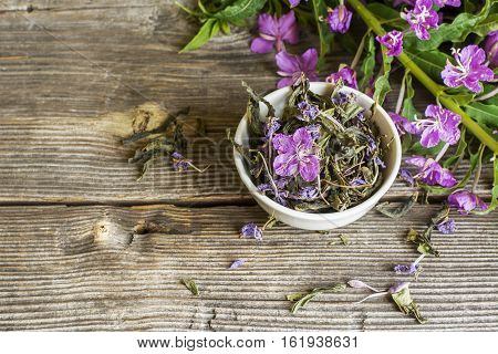 blooming Sally, collected and dried brewing herbal tea useful scattered on the wooden background with flowers and a cup of tea. selective Focus poster