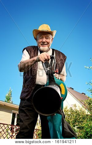 Autumn in a garden. Senior man removes fallen leaves in his garden using leaf blower.
