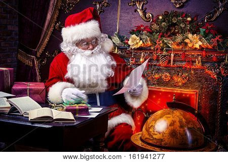 Santa Claus at home reading the post and plans to travel around the planet. Christmas time. Time for miracles.