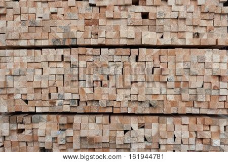 A lot of ends of square section wooden pine bars as background.