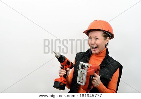 Cheerful smiling woman construction worker with electric screwdriver and tools in the hands of a fret saw