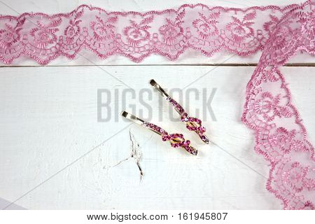 Golden hairpins with pink gemstone and pink lace on white wood