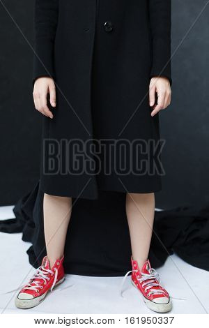 Girl Standing In A Black Coat And Red Sneakers. Careless Lifestyles