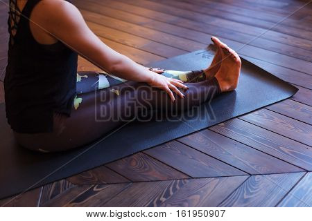 girl sits on a mat with straight legs doing yoga