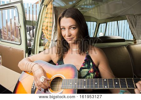 A beautiful girl plays the guitar while sitting in the back of her classic combi van.