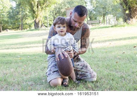 Tattooed Father Have Fun With His Son In The Park With Rugby Ball