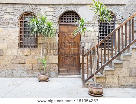 Facade of historic House with wooden closed door and two window with interleaved wooden grid and stair with wooden handrail, Medieval Cairo, Egypt