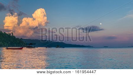 Huge White Clouds above Diving Station on Sunset, Moon in Sky, Homestay Gam Island, West Papuan, Raja Ampat. Indonesia