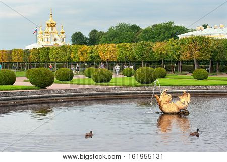 Peterhof, Saint - Petersburg, Russia - August 19, 2016: People walk in The Upper Garden. On the background is The Palace Church of Saints Peter and Paul. Foreground is fragment of The Mezheumny (Indefinite) Fountain.