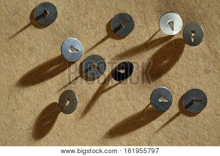 old metal thumbtacks on a yellow background
