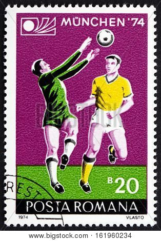 ROMANIA - CIRCA 1974: a stamp printed in Romania shows Players in Action Soccer and Games Emblem World Cup Soccer Championship Munich circa 1974