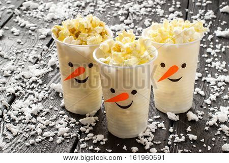 Plastic cups in the form of funny snowmen with popcorn. Homemade applique on plastic cups. The idea for the Christmas party. DIY concept Merry Christmas and Happy New Year