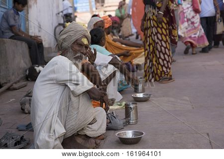 Mathura, Agra, India - October 13, 2016: Line of beggars seeking alms from worshipers outside a temple in Mathura, India.