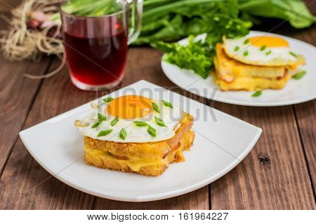Croque-Madame, a French sandwich with greens and berry juice for breakfast. Wooden table. Top view