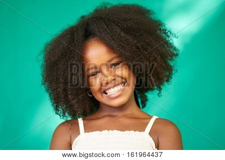 Portrait of Cuban children with emotions and feelings. Black young girl from Havana Cuba smiling looking at camera with joyful and funny expression.