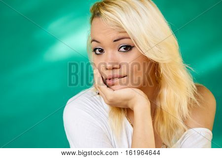 portrait of woman thinking and biting her lips looking up with hand on cheek. Horizontal shape Copy space