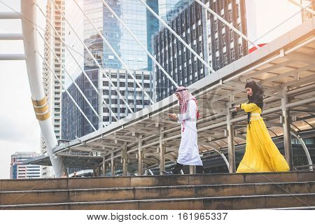 Young Muslim business man holding smart phone and walking rapidly to airport and Young Muslim business women Women looking her watch In rush hour at stairway in urban. Business in the city concept.