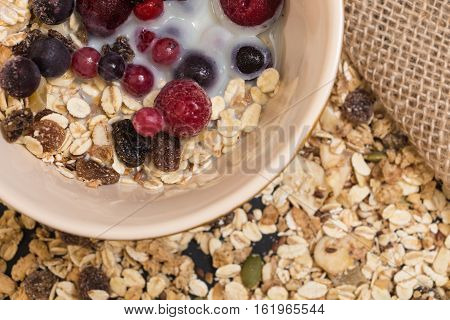 Bowl Of Muesli With Frozen Berries And Plant Milk Closeup Background