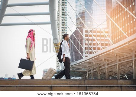 Young Muslim business man holding a bag and business man walking to airport In rush hour at stairway in urban. Business in the city concept.