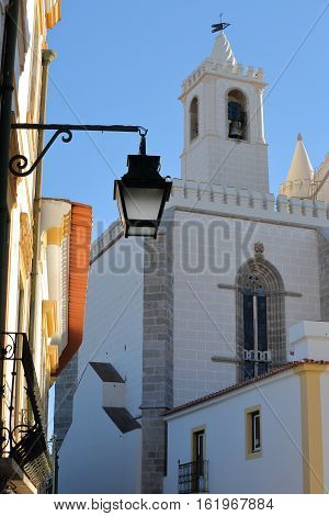 EVORA, PORTUGAL:  A street lamp with Sao Francisco Church in the background