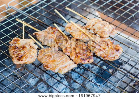 Grilling pork satay on the steel grate