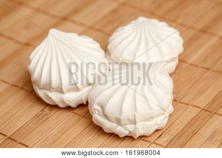Closeup of three white sweet airy zephyrs on bamboo napkin