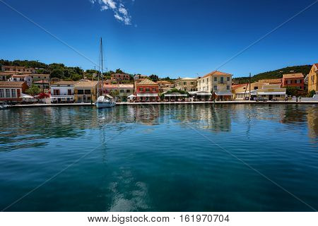 The Island of Paxos, Greece, 22 May, 2016: Early summer of the Island of Paxos - The Port of the Island of Paxos with buildings and boats around it.