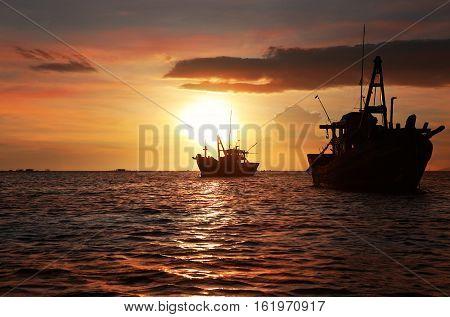 Dark silhouettes of anchored fishing boats in the setting sun. Mui Ne Vietnam