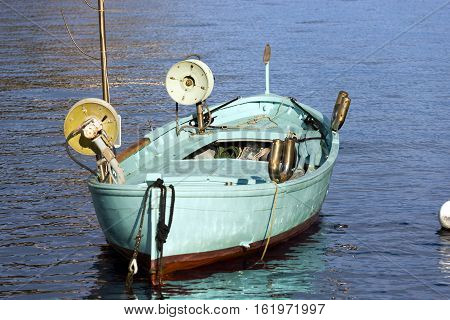 Small wooden turquoise fishing boat with two winches for the fishing nets moored in the port of Portofino. Genova Liguria Italy