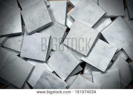 Many small square tiles of white Carrara marble. Tuscany Italy