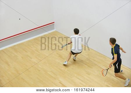 Squash players in action on squash court, back view.