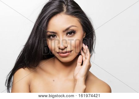 Beautiful diverse woman with gorgeous face, dark luscious hair and glowing skin on her bare shoulders