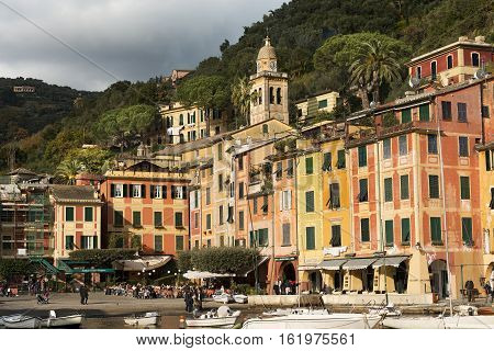 PORTOFINO ITALY - DECEMBER 9 2016: People in the square of the village of Portofino with the colorful houses and the church of St. Martin. Genova Liguria Italy