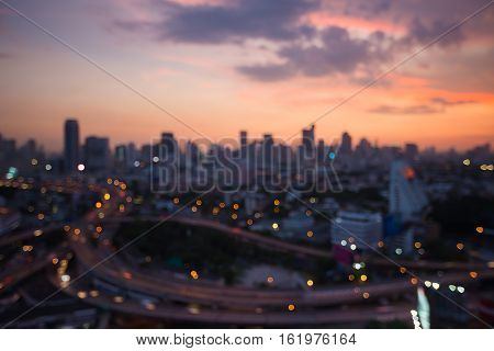 Abstract blurred lights city and highway interchanged with sunset sky background