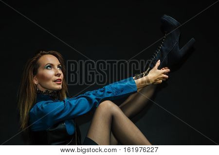 Firearm fashion victorian elegant concept. Vintage girl fixing footwear. Steampunk lady sitting on floor holding her shoe next to antique weapon.