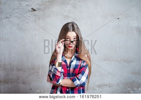 Portrait of watchful woman in the red checkered shirt with eyeglasses on the gray textured wall background