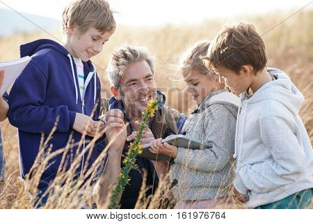 Teacher taking kids to countryside to explore plants and flowers