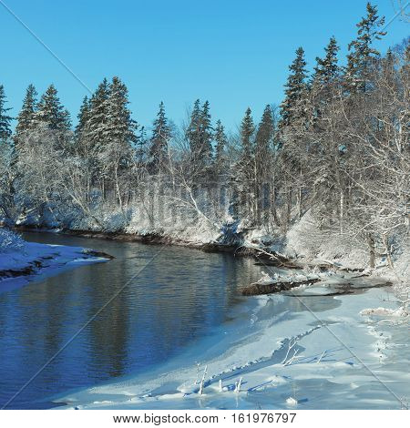 The curve in a peaceful river in the winter landscape of rural Prince Edward Island, Canada.